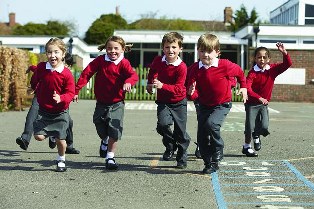 Children in their school uniform running